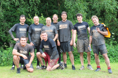 Members of staff from Briggs Equipment celebrate after completing the JCB Mud Run.